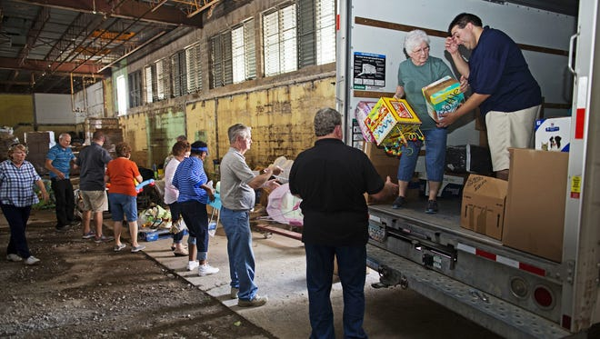 Westwego Senior Center coordinator Brant Fonseca, right, leads a team of volunteers as they unload a truck full of donated goods to be distributed to flood victims through the Healing Place Church in Denham Springs.