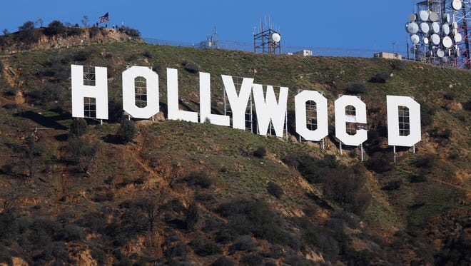 """Los Angeles County firemen remove banners from the letters on the Hollywood sign, seen vandalized Sunday, Jan. 1, 2017. Los Angeles residents awoke New Year's Day to find a prankster had altered the famed Hollywood sign to read """"HOLLYWeeD."""" Police have notified the city's Department of General Services, whose officers patrol Griffith Park and the area of the rugged Hollywood Hills near the sign. California voters in November approved Proposition 64, which legalized the recreational use of marijuana, beginning in 2018."""