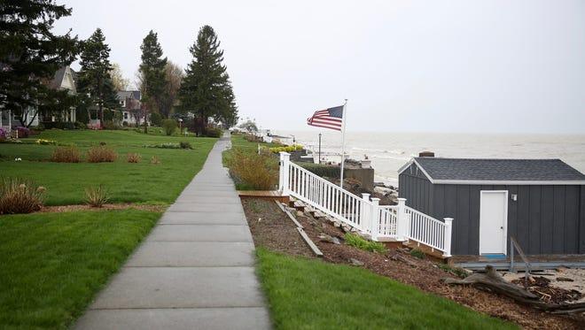 A public sidewalk behind houses on Beach Avenue runs along Lake Ontario.