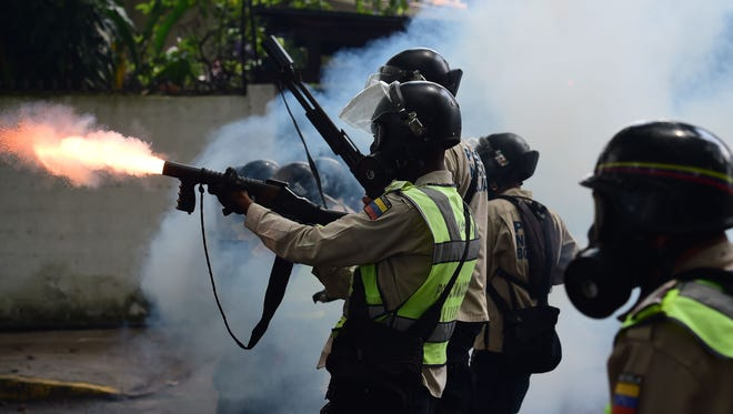 Venezuelan police clash with opposition activists during a march against President Nicolas Maduro, in Caracas on May 1, 2017.