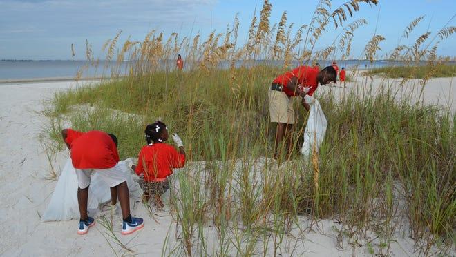 Volunteers pick up litter at a Lee County beach during last year's Coastal Cleanup. Keep Lee County Beautiful needs volunteers for this year's rescheduled Coastal Cleanup on Saturday.