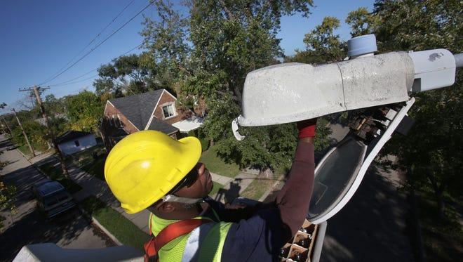 Public lighting worker installs new LED lights
