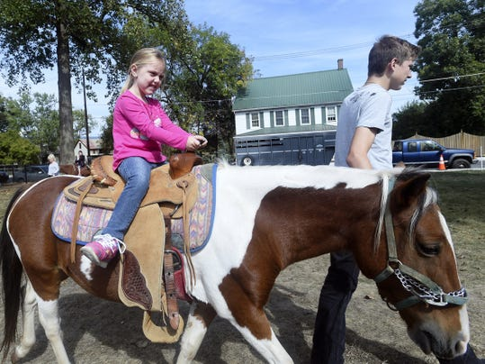 Brooklynne Greasley, 5, takes a ride on a pony during Mercersburg Townfest in downtown Mercersburg on Saturday.