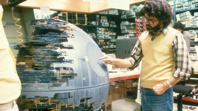 George Lucas inspects the Death Star model during filming of his 'Star Wars' epic.