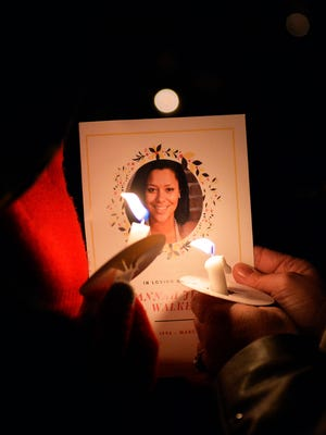 Mourners hold a copy of a program during the candlelight vigil for Savannah Jeanne Walker on the lawn of Grawmeyer Hall on the University of Louisville campus, Wednesday, March. 22, 2017 in Louisville Ky.
