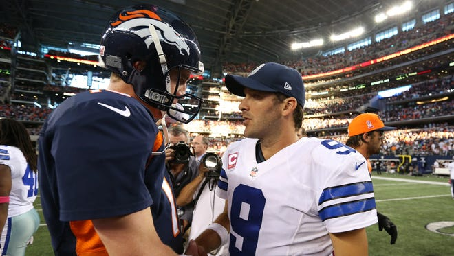 Denver Broncos quarterback Peyton Manning (18) meets with Dallas Cowboys quarterback Tony Romo (9) at the end of the game at AT&T Stadium.  The Denver Broncos beat the Dallas Cowboys 51-48.