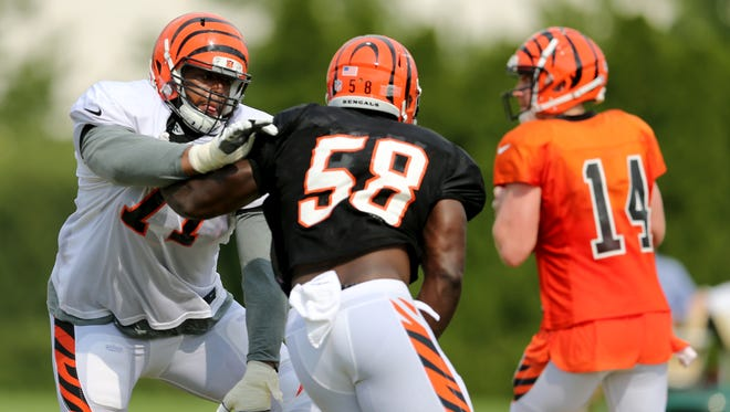 Cincinnati Bengals offensive tackle Cordy Glenn, left, blocks defensive end Carl Lawson (58) as he rushes toward quarterback Andy Dalton during training camp.