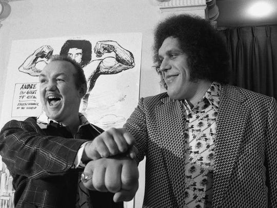 In this May 4, 1976, file photo, heavyweight boxer Chuck Wepner, left, compares fists with professional wrestler Andre The Giant in New York.