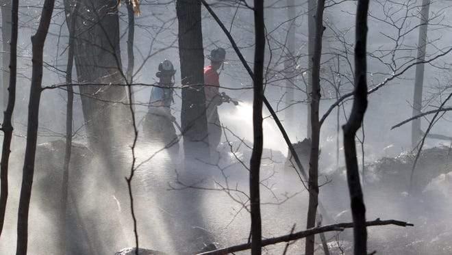 Somers firefighters with the help of several northern Westchester and Putnam departments battle a large brush fire that scorched over 5 acres off Lovell Street in Somers April 20, 2016.