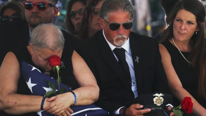 The family of Fort Myers police officer Adam Jobbers-Miller react at his funeral at Germain Arena on Monday.