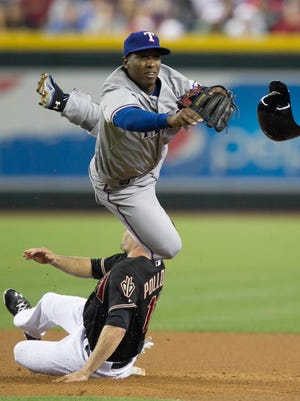 Rangers infielder Jurickson Profar knocks the helmet off Diamondbacks baserunner A.J. Pollock while trying to complete a double play at Chase Field in Phoenix on May 27, 2013.