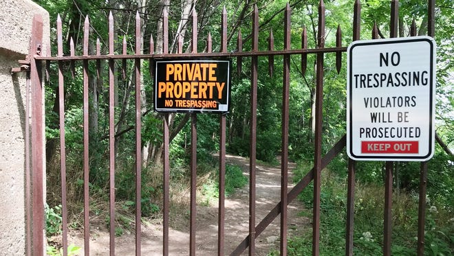 "Riverside Cemetery has posted ""No trespassing"" signs on both ends of a trail on its property. The cemetery encourages people to use the cemetery's paved roads instead."
