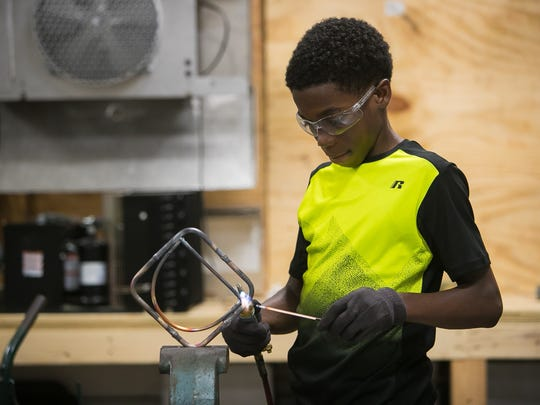 Dean Shepherd, 13, molds copper as New Castle County middle schoolers in 6th and 7th grades learn technical skills at the Build Your Future! Construction Technologies Camp held at Delcastle Technical High.