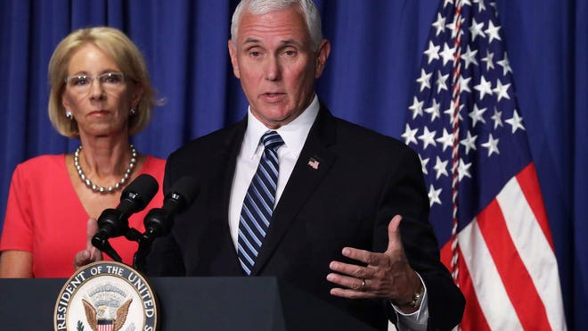 Vice President Mike Pence speaks as Secretary of Education Besty Devos listens during a White House Coronavirus Task Force press briefing at the U.S. Department of Education July 8, 2020.