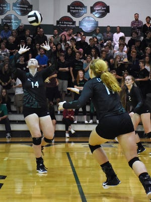 Emmy Chambers (14) plays a pass to Hannah Meyers (middle) during a match with South Walton on Nov. 1, 2017.