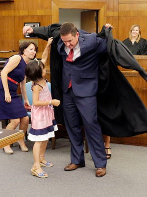 Newly sworn in Sheboygan County Circuit Court Judge Daniel J. Borowski gets some help from his daughters Annalise, left, and Elle (hidden), Friday August 12, 2016 during the Investiture of Daniel J. Borowski as a Sheboygan County Circuit Court Judge.