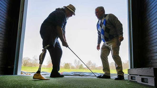 Air Force veteran Tom Zimmerman takes part in a lesson with help from golf pro Jack Barber as part of the PGA Hope program at the Highland Golf and Country Club Wednesday, April 18, 2018. The PGA Hope program helps veterans get back into the swing of golfing with the help from many local golf professionals and courses.