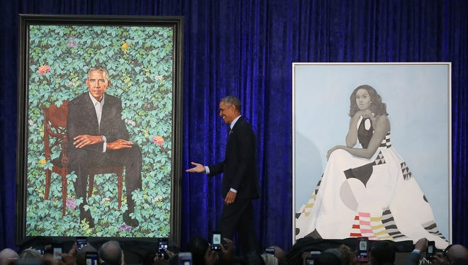 Former president Barack Obama stands with his and former first lady Michelle Obama's newly unveiled portrait during a ceremony at the Smithsonian's National Portrait Gallery, on Feb. 12, 2018, in Washington, D.C.
