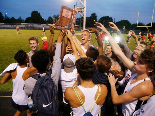 The Harrison Raiders celebrate winning the boys track
