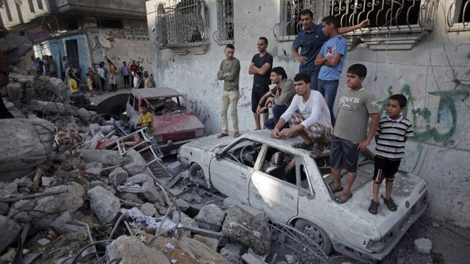 Palestinians look at a destroyed house where five members of the Ghannam family were killed in an Israeli missile strike early Friday morning in the Rafah refugee camp in the southern Gaza Strip