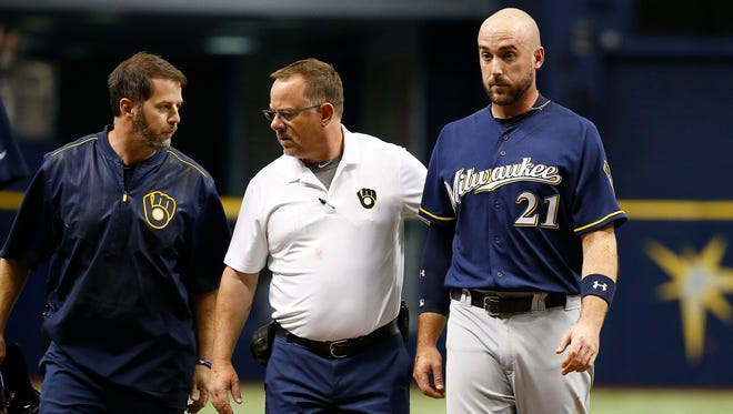 Brewers third baseman Travis Shaw is helped off the field after being hit on an attempted steal of second base.