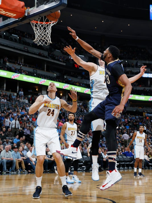 New Orleans Pelicans forward Anthony Davis, right, shoots as Denver Nuggets center Mason Plumlee, back left, and forward Nikola Jokic, of Serbia, defend during the first half of an NBA basketball game Friday, April 7, 2017, in Denver. (AP Photo/David Zalubowski)