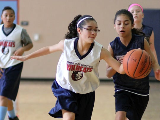 The Deming Youth Basketball League celebrated its most successful season on the hardwoods by hosting a post-season tournament for all grade levels. In the girls' fifth- and sixth-grade division, Bianca Valverde chases down a loose ball in a tightly contested championship game. In the boys' fifth- and sixth-grade division, Kye Carbajal eyes the basket with the long arm of Martin Granillo waiting to defend.