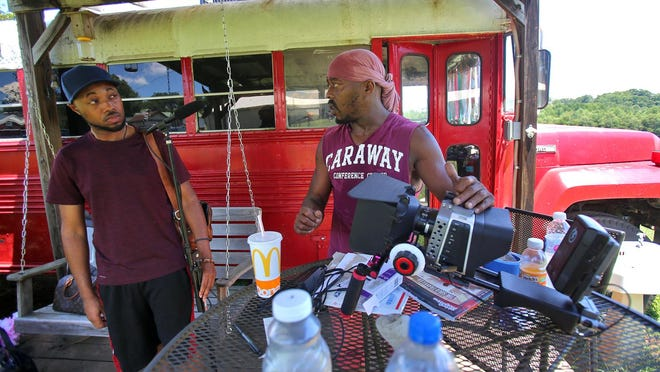 """From left, sound engineer Tomorris Ellis and director Walt """"Walt Diddy"""" Wray talk on the set of """"Justice through Redemption"""" at the red bus off Old Boiling Springs Road."""
