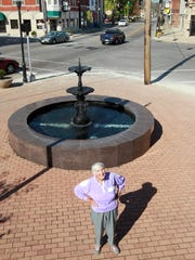 Opal Evans stands at Ritte's Corner in Latonia, where she and her husband ran a jewelry business for decades in one of the buildings in the block behind her.