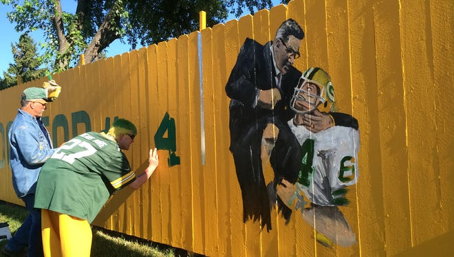 Christopher Handler and Dale Decker paint a fence in honor of Jerry Kramer across from Lambeau Field Saturday