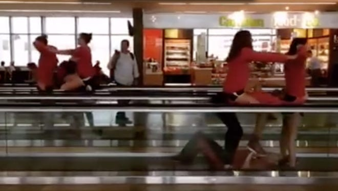 University of Louisville women's swimmers created pedway performance art at Raleigh-Durham airport