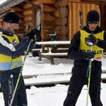 In this photo taken on Dec. 4, 2013, guide Patrick Viljaan, left, helps blind biathlete Steve Baskis get ready for a training session at the Frisco Nordic Center in Frisco, Colo.