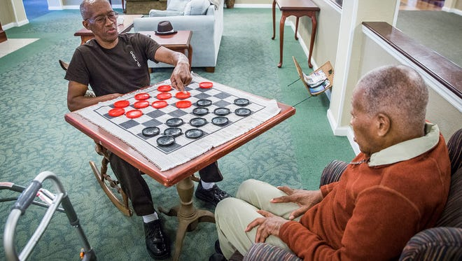 Carl Kizer Jr. plays checkers with his father at Lynd Place Nursing Home Thursday afternoon.
