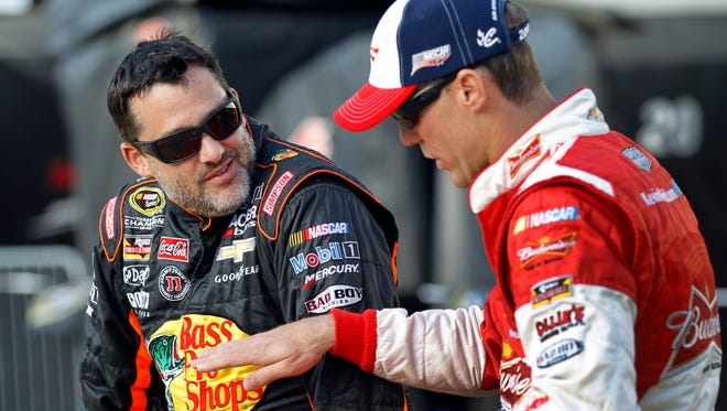 Tony Stewart, left, talks with Kevin Harvick before qualifying for Sunday's NASCAR Sprint Cup series auto race at Charlotte Motor Speedway in Concord, N.C., May 22, 2014.