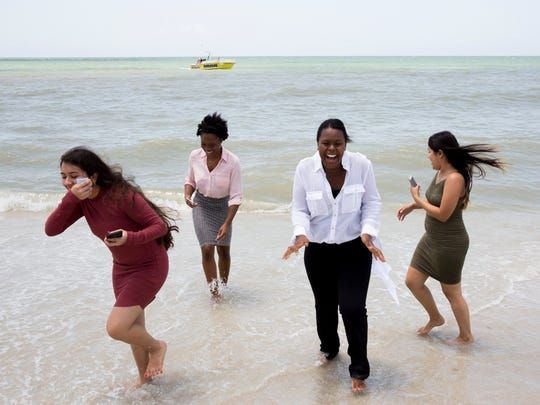 Cindy Velazquez, 15, from left, Azariah Howard, 18, and Brenda Ponce, as well as another student with the program, share a laugh as they dip their toes into the Gulf of Mexico near the conclusion of their tour of the Ritz-Carlton, Naples on Thursday, Aug. 3, 2017. The young women, along with 20 other area students, were part of the inaugural Corporate Development Program with Taste of Immokalee.
