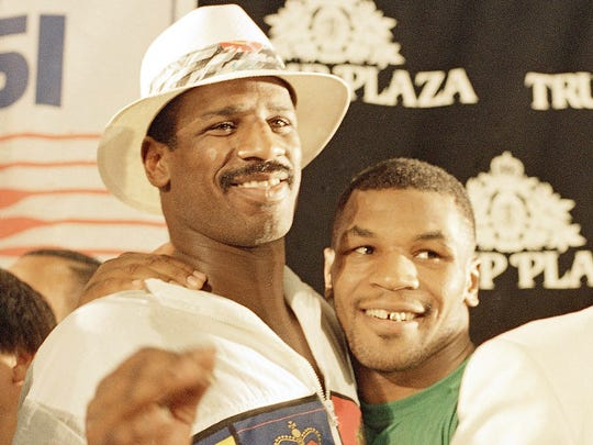 Mike Tyson, right, embraces Michael Spinks at a post-fight news conference in Atlantic City, Monday, June 28, 1988. Tyson knocked out Spinks in the first round of their world heavyweight championship fight. (AP Photo/Rusty Kennedy)