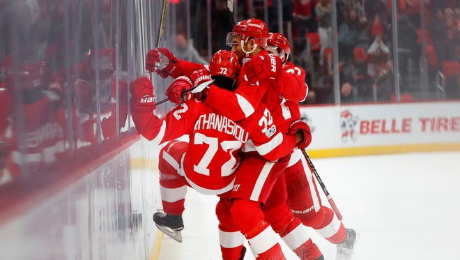 Red Wings' Andreas Athanasiou is mobbed by teammates as he celebrates his overtime goal to defeat the Senators, 2-1, at Little Caesars Arena on Wednesday, Jan. 3, 2018.
