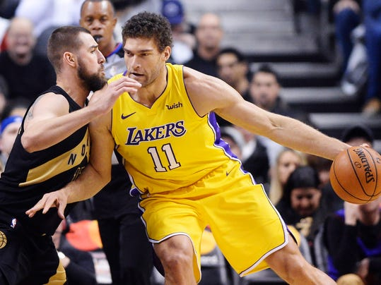 Los Angeles Lakers center Brook Lopez (11) protects the ball from Toronto Raptors center Jonas Valanciunas (17) during first-half NBA basketball game action in Toronto, Sunday, Jan. 28, 2018. (Frank Gunn/The Canadian Press via AP)