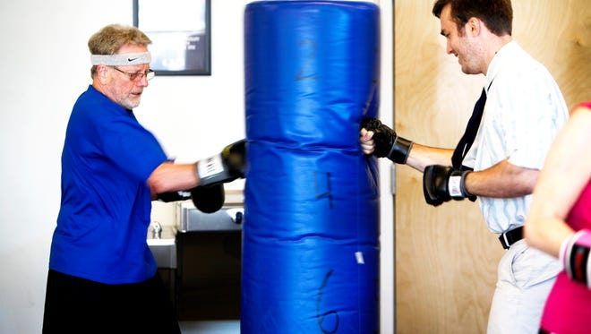 "Robert Debrecht, left, punches a bag with physical therapist and clinical director Sean Simonds at Specialized Physical Therapy December 1, 2016 during a ""Knock Out Parkinson's"" workout."