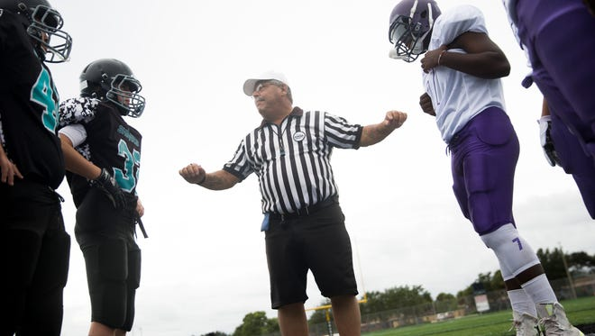 """Collier County sports official Carmine DeCianni brings Cypress Lakes, right, and North Naples Youth Sharks players together before their match-up at Gulf Coast High School on Saturday, Aug. 26, 2017, in North Naples. DeCianni is waiting for a new kidney. """"I work full time. I officiate full time. Other than that, I'm on dialysis at home,"""" DeCianni said."""