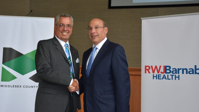 Middlesex County Freeholder Director Ronald G. Rios and Barry H. Ostrowsky, President and Chief Executive Officer, RWJBarnabas Health, shake hands to mark the announcement of a partnership regarding the County's two long-term care facilities.