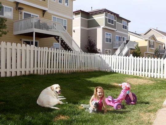 Addyson plays in the backyard with her therapy dog,