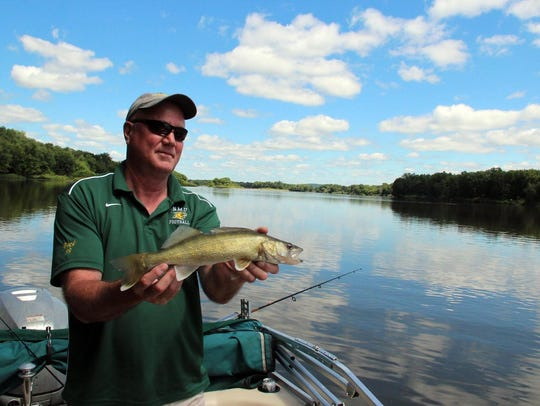 Mark Peck holds a 17.5 inch walleye before releasing