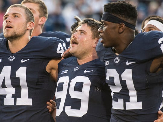 Penn State Nittany Lions place kicker Joey Julius (99) sings the Penn State alma mater as he embraces Penn State Nittany Lions long snapper Zach Ladonis (41) and Penn State Nittany Lions cornerback Amani Oruwariye (21) after Penn State the home opener against Kent State on Saturday, Sept. 3, 2016 where Penn State won 33-13.
