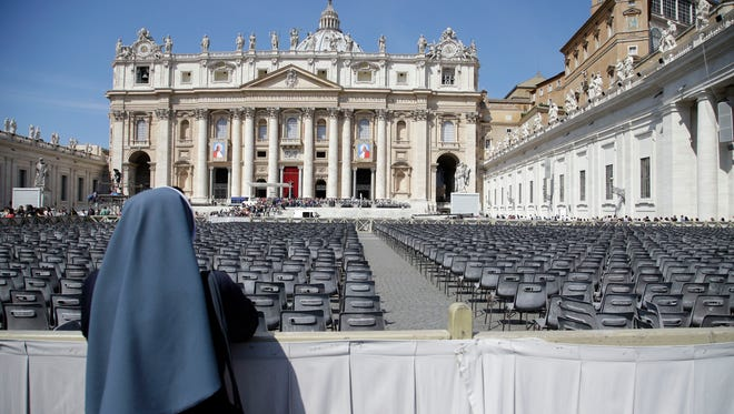 A nun looks at the tapestries showing late Pope John Paul II, left, and Pope John XXIII hanging from the facade of St. Peter's Basilica in St. Peter's Square at the Vatican on April 25, 2014.