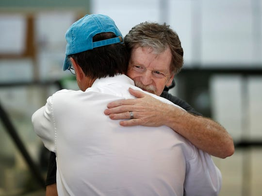 Baker Jack Phillips, owner of Masterpiece Cakeshop, left, is hugged by a man  June 4, 2018, in Lakewood, Colo., after the U.S. Supreme Court ruled that he could refuse to make a wedding cake for a same-sex couple because of his religious beliefs did not violate Colorado's anti-discrimination law.  The majority ruling was 7-2 in the closely watched case.
