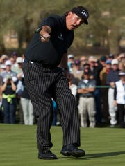 Phil Mickelson watches his birdie putt circle the hole