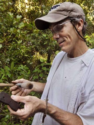 Archaeologist and anthropology professor Keith Ashley examines a piece of pottery between 1,200 and 1,500 years old.