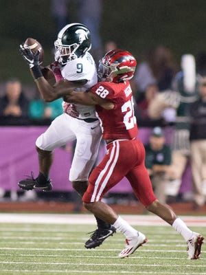 Michigan State Spartans wide receiver Donnie Corley (9) catches the ball while Indiana Hoosiers defensive back A'Shon Riggins (28) tackles him in the second half of the game at Memorial Stadium.