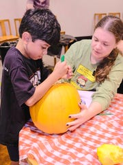 Noah Mahintorabi, 8, and Michelle Hostetter with the Germantown Library team up for one of the pumpkins tackled by participants on Sunday.
